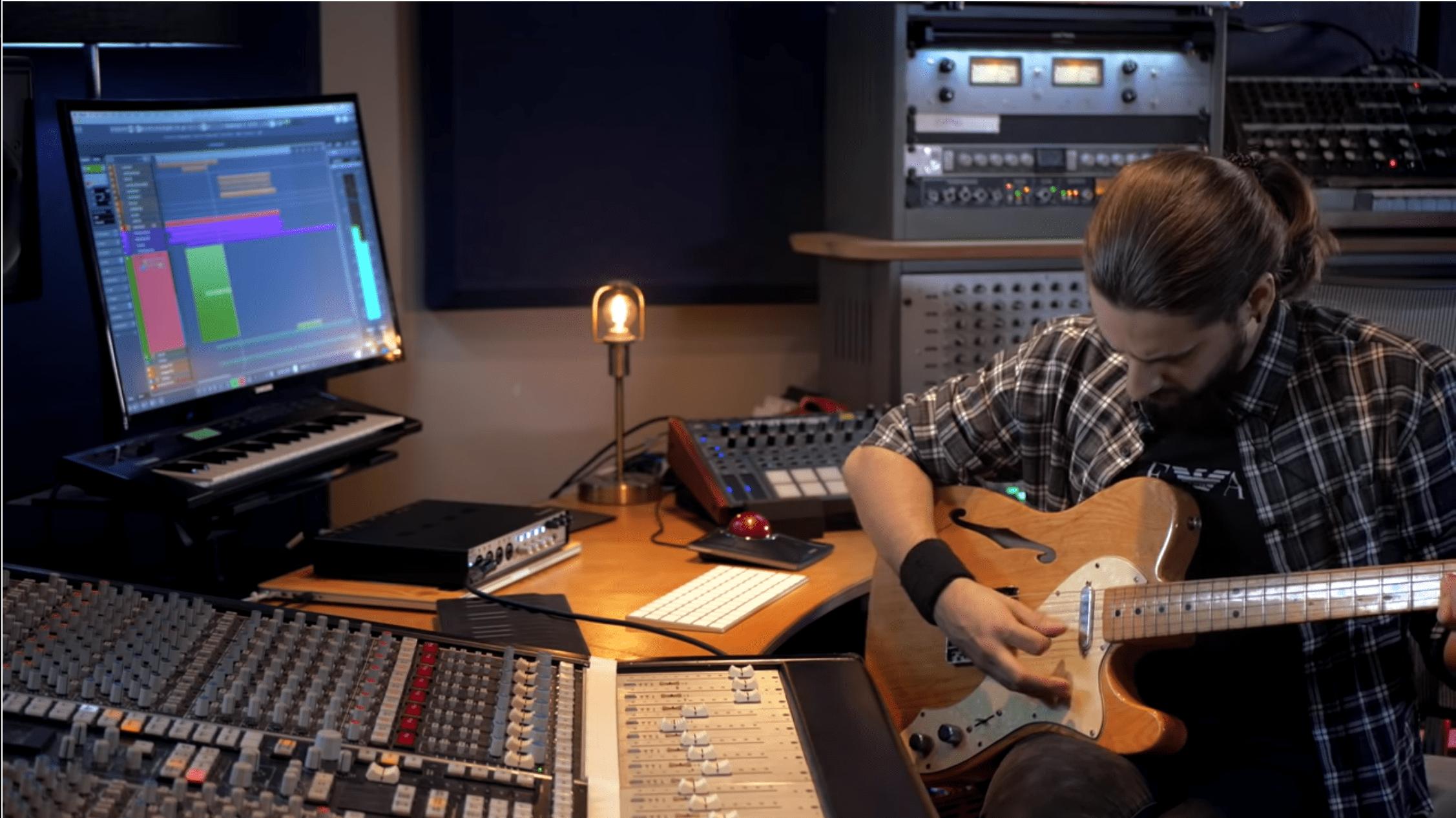 Guitarrista en estudio de sonido grabando con guitarra en Cubase
