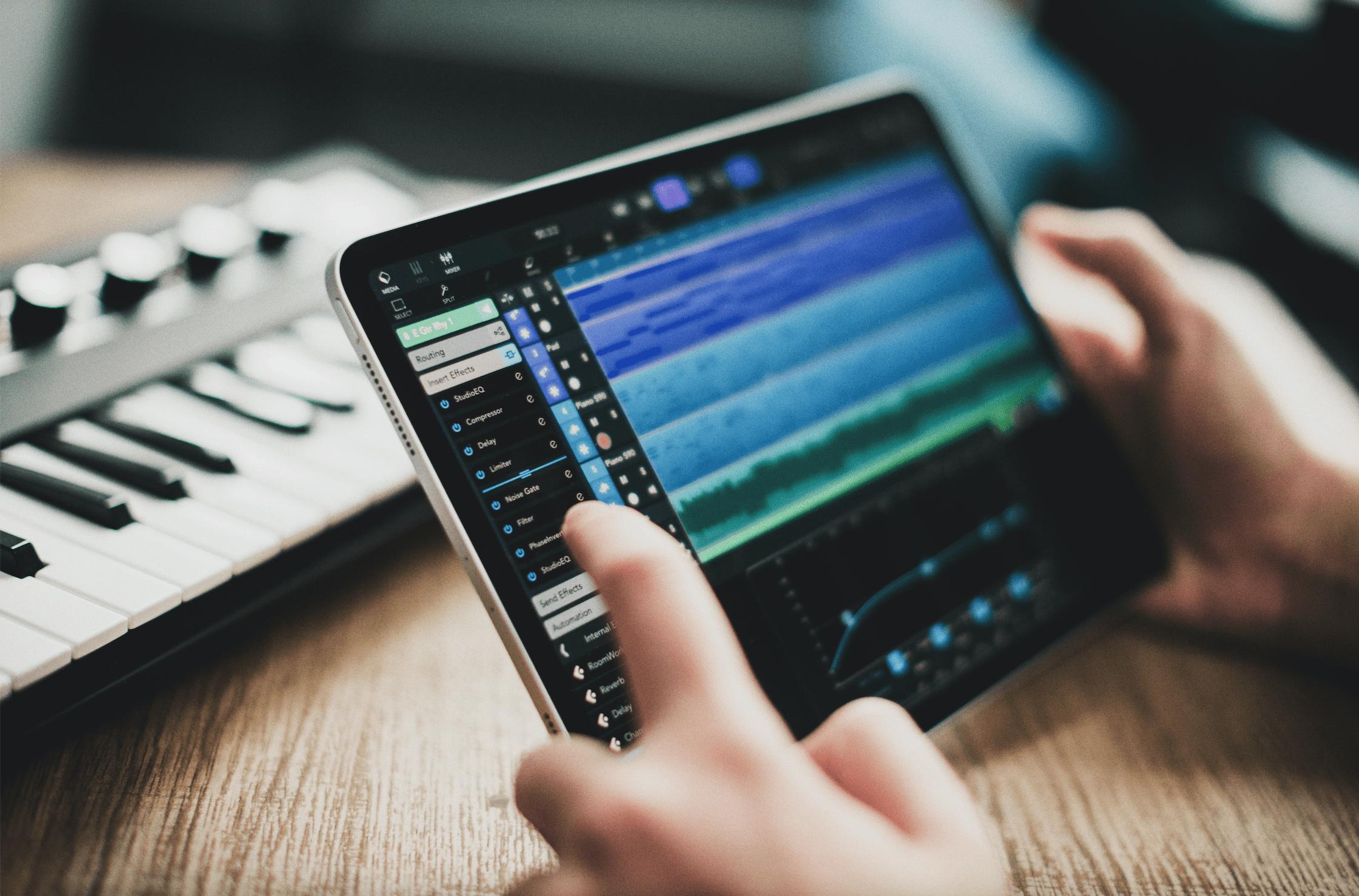 Manos sujetando ipad con Cubasis 3 y teclado